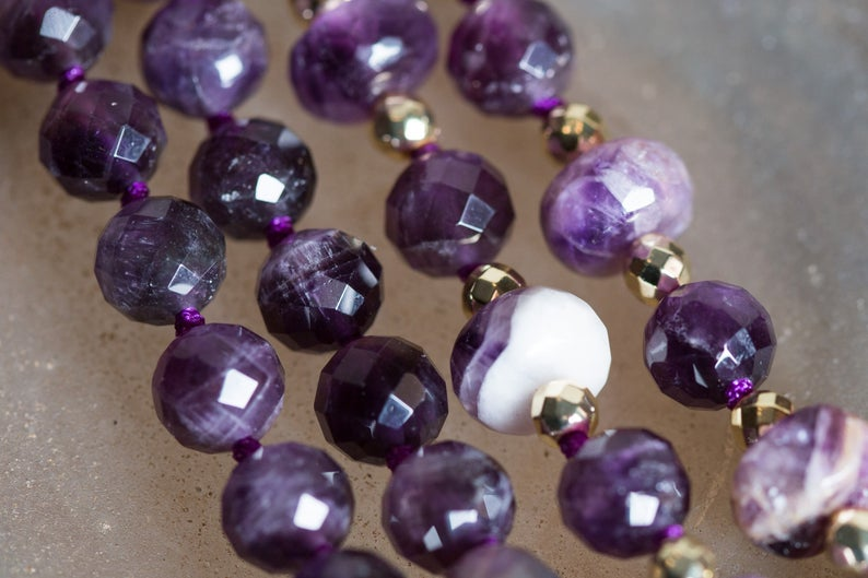 This necklace is made with natural Amethyst faceted and rondelle beads. Among them, there are golden Hematite beads that highlight the deep shine of Amethyst. It's fully hand-knotted with a purple cord, assigning strength and durability while the design completes with a gold-plated cubic zirconia box clasp with a heart symbol.