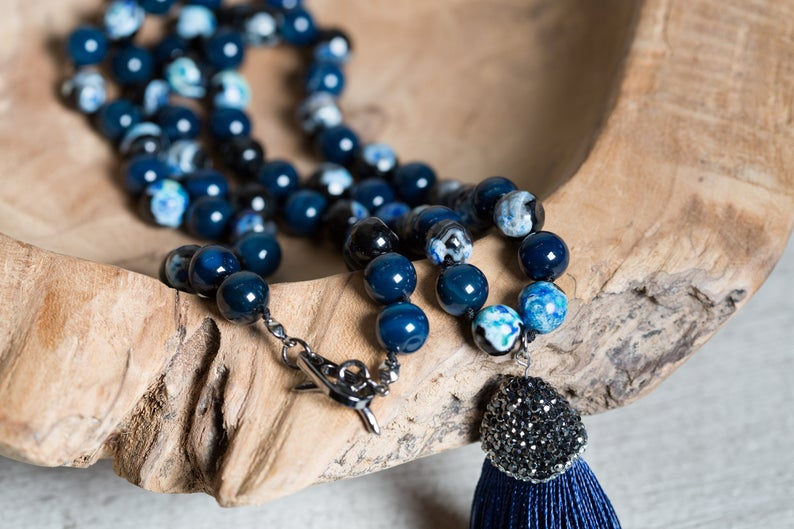 Blue Agate beaded necklace with paved tassel placed on a wooden bowl.
