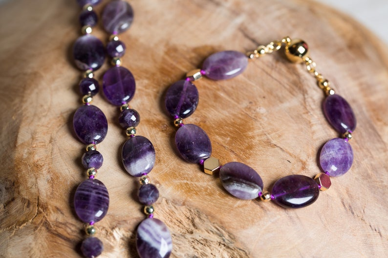 This beautiful beaded bracelet is flawlessly made with natural Amethyst oval beads. Among them, there are golden Hematite hexagon flat beads that highlight the deep shine of Amethyst. It's fully hand-knotted with a purple cord, assigning strength and durability while the design completes with a magnetic ball clasp.  It's worth mentioning that all findings are made of 18ct gold plated, 925 sterling silver, adding luxury and elegance to this queenly design.