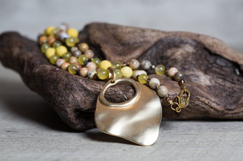 Yellow Agate beaded necklace with a large golden pendant, placed on a piece of wood. Beautiful statement necklace for summer.