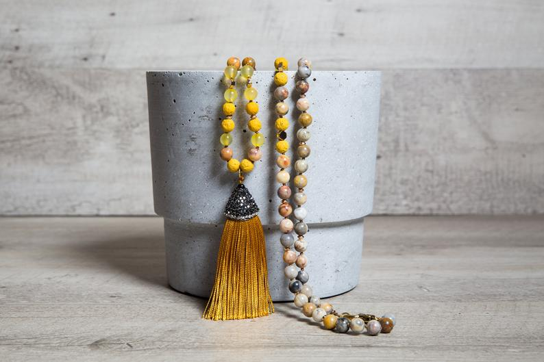 Long beaded necklace made with yellow crazy lace Agate beads and a musturd yellow tassel with paved cap.