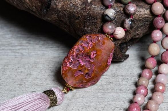 Large raw Agate pendant in pink color, part of a Rhodonite mala necklace.